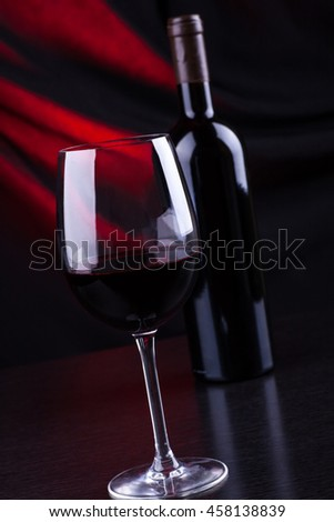 Glass and bottle of red wine with a dark background lit by a red light