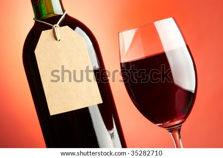 Glass and bottle of red wine with tag - stock photo