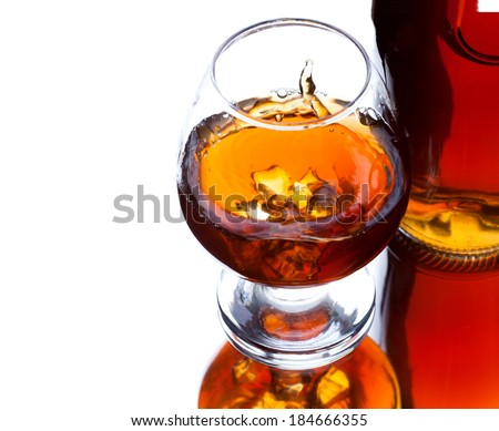 Glass and bottle of whiskey with splash and with reflection on light background, selective focus on the glass, space for text - stock photo