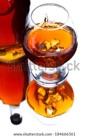 Glass and bottle of whiskey with splash and with reflection on light background, selective focus on the glass - stock photo