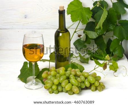 glass and bottle of white wine with grapes on a wooden table