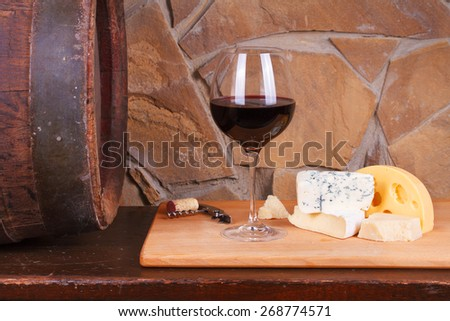 Glass and bottle of wine, cheese and prosciutto, old wooden barrel