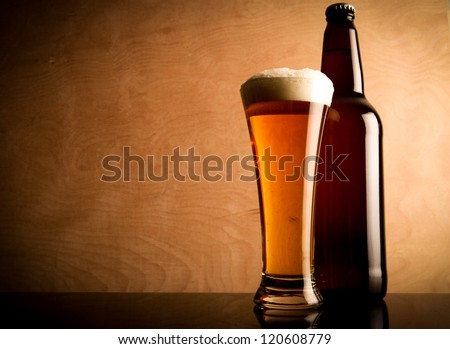 Glass and bottle with beer on the table - stock photo