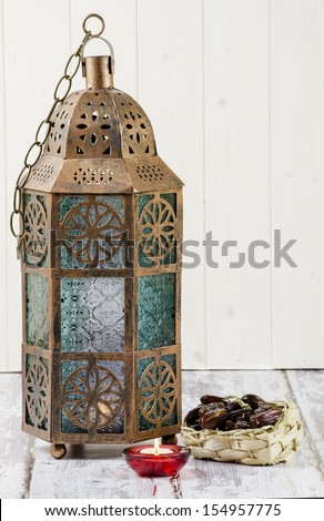 Glass and bronze coloured metal lantern with candle and basket of dates - stock photo