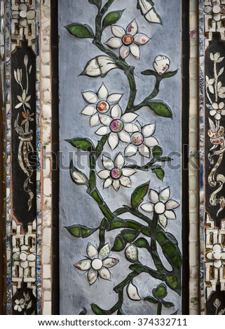 Glass and ceramic white flower mosaics decorating the columns of the palaces of the Imperial City or Citadel, Hue, Vietnam. - stock photo