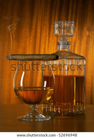 Glass And Decanter Of Whisky With A Cigar On A Table