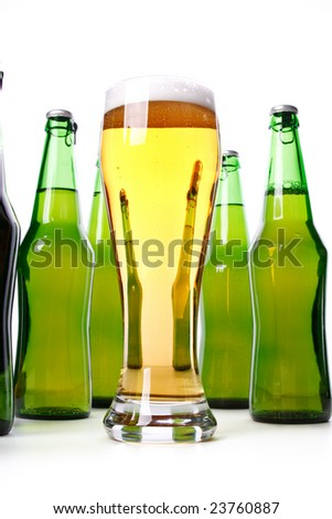 Glass and green bottle of beer on a white background