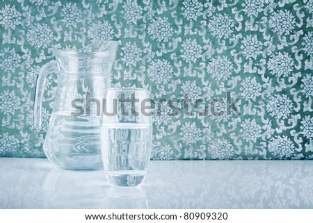 glass and jug filled with fresh water on patterned backdrop