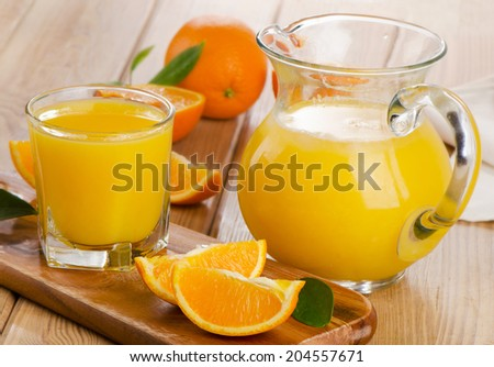 Glass and jug of  orange juice with sliced orange. Selective focus