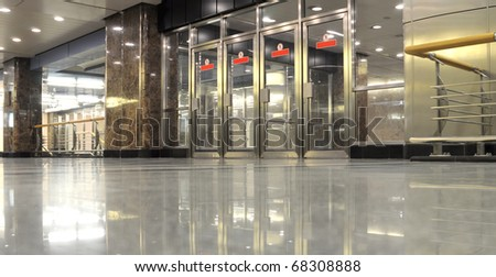 Glass and metal doors in undegrond hall - stock photo