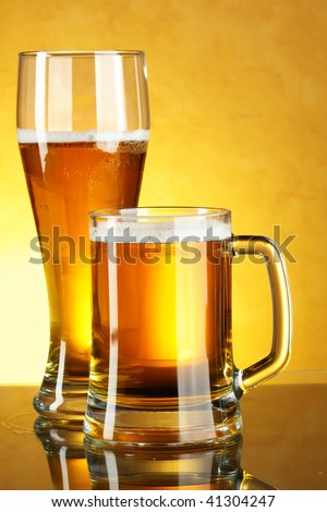 Glass and mug of beer over yellow background
