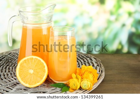 Glass and pitcher of orange juice on wooden table, on green background