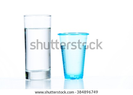 Glass and plastic cup with water - stock photo