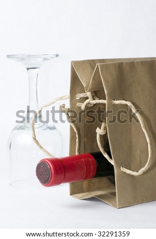 Glass and red wine bottle in paper bag - stock photo
