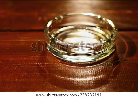 Glass ashtray on wooden table - stock photo