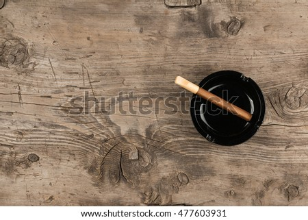 Glass ashtray with cigar stands on a wooden surface, can be used as background