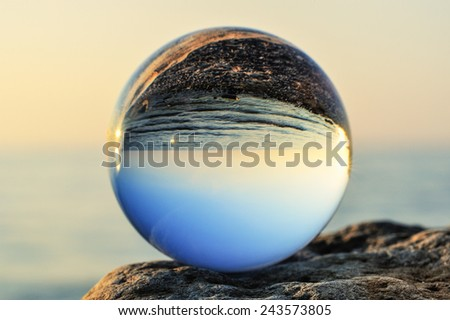 Glass ball on the boulder at the sea - stock photo
