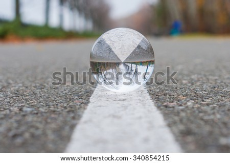 Glass ball or orb for fortunetelling, soothsaying and predicting the future. on textured surface and white line background with empty space. - stock photo