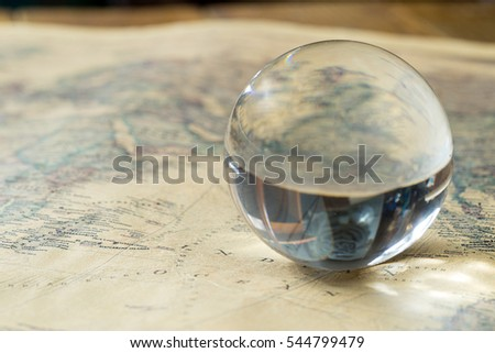 glass ball, sphere on old vintage map, macro background