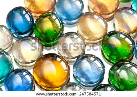 Glass balls marbles abstract colored mix on white background, color beads with window light reflections, colorful abstract in horizontal orientation, nobody. - stock photo