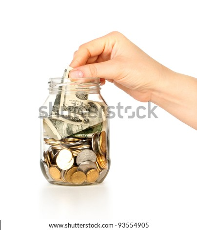Glass bank for tips with money and hand put dollars isolated on white - stock photo