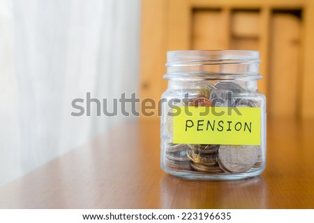 Glass bank with many world coins and pension word or label on money jar over table - stock photo