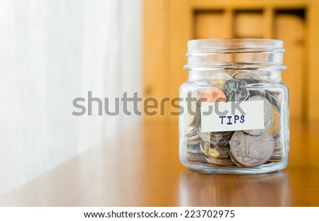 Glass bank with many world coins and  tips word or label on saving money jar - stock photo