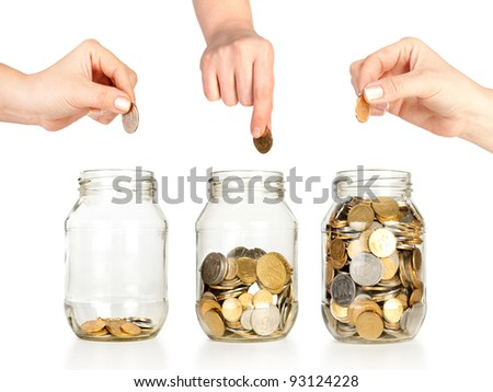 Glass banks for tips with money like diagram and hands put coins isolated on white - stock photo