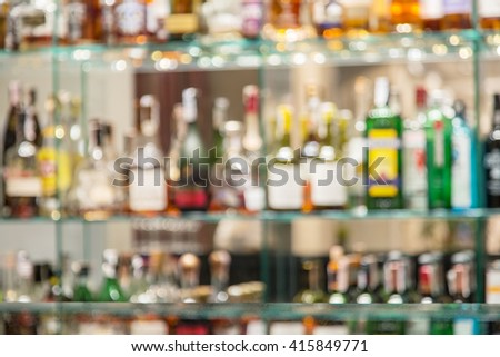 Glass bar counter with blurred shelves with alcohol bottles on the background. - stock photo