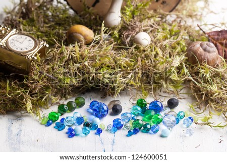 glass beads with mushrooms, clocks, moss and shells on white wooden table - stock photo