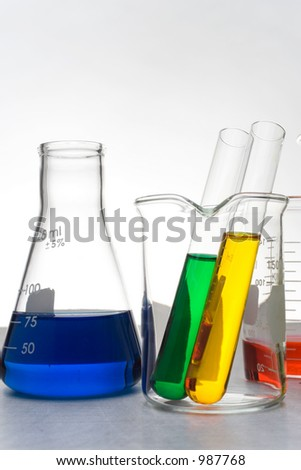 Glass beakers filled with colored liquid - stock photo