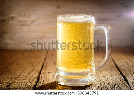 Glass beer on wood background with copyspace - stock photo