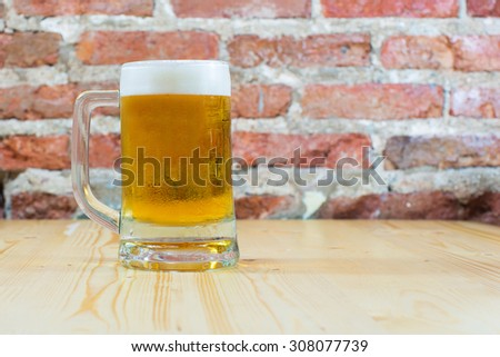 Glass beer on wood/brick background. - stock photo
