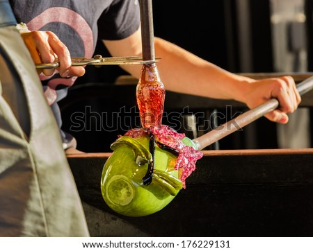 Glass blower artists work on adding decoration to ornate green glass bottle or bowl - stock photo