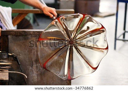 Glass blower forming a piece of decorative glass. (Murano, Italy) - stock photo