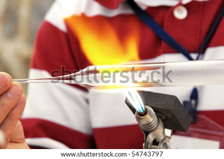 Glass blower heating a bulb on the gas burner - stock photo