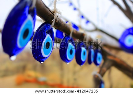 Glass blue Nazars, charms to ward off the evil eye hanging off the branches of a tree in the rain in Turkey  (shallow depth of field) - stock photo