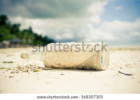 Glass bottle laying on a beach - stock photo
