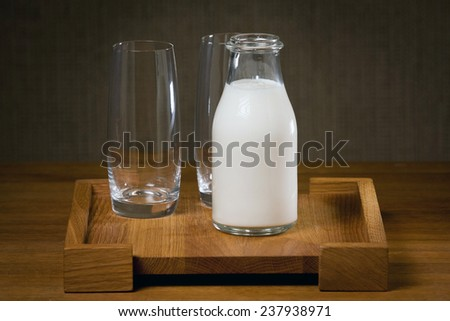 Glass bottle of ayran (turkish yogurt drink) on the wooden table - stock photo