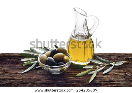Glass bottle of premium virgin olive oil and some olives with leaves on wooden background isolated - stock photo
