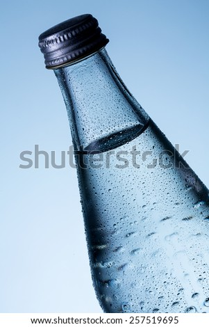 Glass bottle of water with dew drops - stock photo