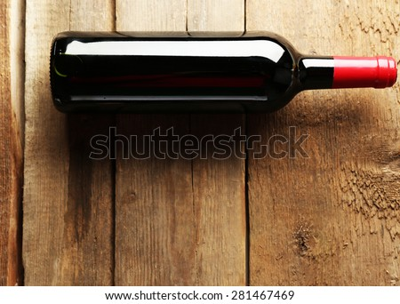 Glass bottle of wine on wooden table background - stock photo