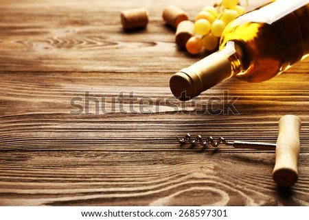 Glass bottle of wine with corks, corkscrew and grapes on wooden table background - stock photo