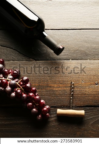 Glass bottle of wine with corkscrew and grapes on wooden table background - stock photo