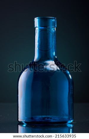 Glass Bottle on a Dark Blue Background - stock photo
