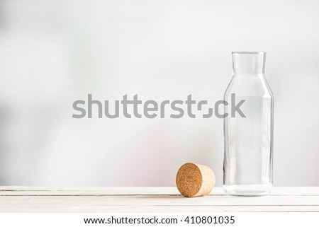 Glass bottle with a brown cork on a wooden table - stock photo