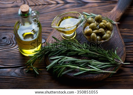 Glass bottle with olive oil, olives and rosemary, studio shot