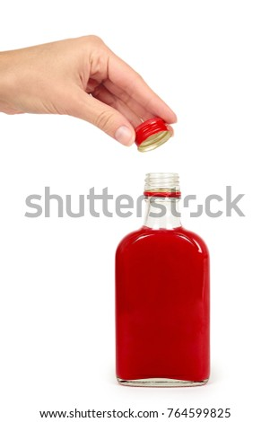 Glass bottle with red tincture in hand isolated on white background. Alcohol problem.