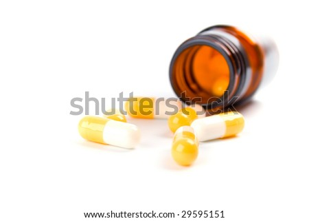 glass bottle with yellow capsules on white background