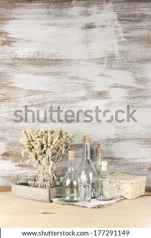 Glass bottles and dry flowers on rustic wooden background. - stock photo